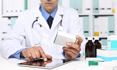 Doctor reading a tablet with medicine boxes in hand